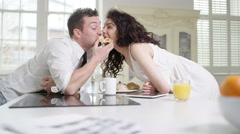 4K Fun couple relaxing in apartment, woman takes a bite of her partner's pastry Arkistovideo