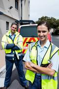 Portrait of ambulance crew front of ambulance car - stock photo