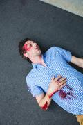 Injured man lying on the ground after accident Stock Photos