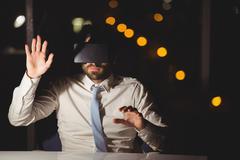 Businessman using virtual reality device at night Stock Photos