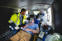 Injured man with ambulance man in ambulance car Kuvituskuvat