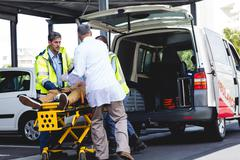 Injured man with ambulance men in ambulance car Kuvituskuvat