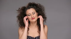 Young brunette with long brown curly hair dancing - stock footage