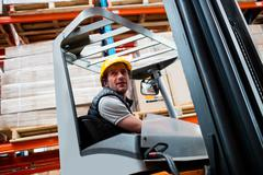 Warehouse worker driving forklift in warehouse Stock Photos