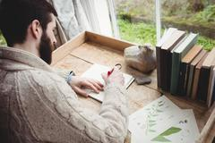 Attractive hipster man drawing at desk in house Stock Photos