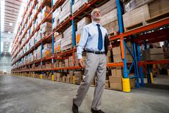 Warehouse manager walking in the aisle of the depot Stock Photos