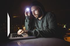 Hacker using a laptop in dark room Kuvituskuvat