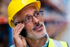 Worker in hard hat using mobile phone in warehouse Stock Photos