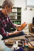 Profile view of cobbler looking the sole of a shoe in his workshop Stock Photos