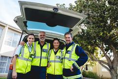 Portrait of a group of ambulancemen front of ambulance car Kuvituskuvat