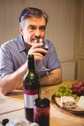 Mature man sitting at table and tasting red wine in his country house Stock Photos