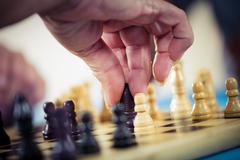 Close up of hands playing chess in a retirement home Stock Photos