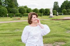 Portrait of positive woman in a white blouse - stock photo