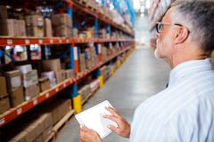 Focus on foreground of warehouse manager taking notes on his tablet computer Stock Photos