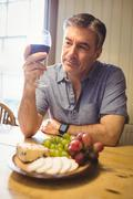 Mature man examining glass of wine in his country house Stock Photos