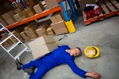 High angle view of unconscious worker lying on the floor in the warehouse Stock Photos