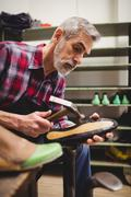 Side view of cobbler hammering on the sole of a shoe in his workshop - stock photo