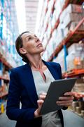 Portrait of warehouse manager looking up and taking notes in depot Stock Photos