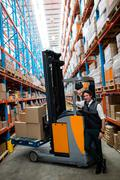 Warehouse worker with forklift in warehouse Stock Photos