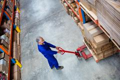 High angle view of man worker pulling the pallet truck in the warehouse Stock Photos