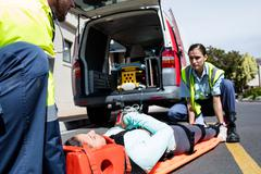 Ambulance men taking care of injured people front of ambulance car Kuvituskuvat