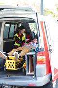 Injured man with ambulancewoman in the ambulance car Kuvituskuvat