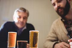 Mature and hipster man looking at shot on the table in country house Stock Photos