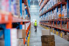 Aisle with a worker at the second plan in warehouse Stock Photos