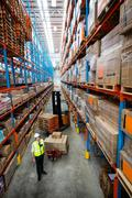 Portrait of a warehouse manager with forklift and pallet truck in warehouse Stock Photos