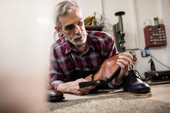 Cobbler hammering on the sole of a shoe in his workshop Stock Photos