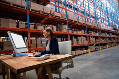 Side view of warehouse manager working on her computer desk in a depot Stock Photos