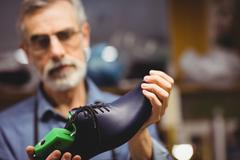 Focus on foreground of a shoe in a workshop - stock photo