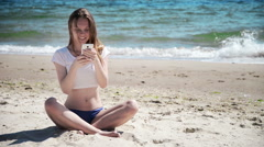 Girl with mobile phone sitting on sand near sea and blue sky. First love Stock Footage