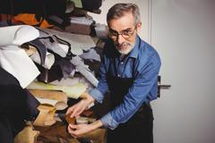 Cobbler posing with a piece of leather in the storehouse Stock Photos