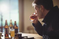 Mature man drinking alcohol in his country house Stock Photos