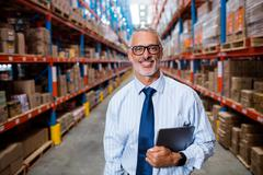 Half length of warehouse manager holding his tablet computer in a depot Stock Photos