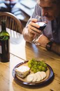Mature man drinking red wine and eating cheese in country house Stock Photos
