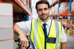 Warehouse manager with yellow coat and scanner in warehouse Stock Photos