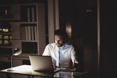 Businessman drawing on graphic tablet at night in the office - stock photo