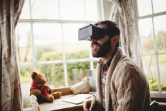 Portrait of hipster man using smart glasses while seating at desk in his hous - stock photo