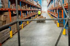 Warehouse worker walking with a pallet truck in warehouse Stock Photos