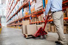 Warehouse manager in aisle with a pallet truck in warehouse Stock Photos