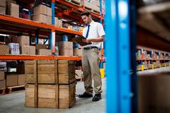 Warehouse manager checking list on his clipboard in warehouse Stock Photos