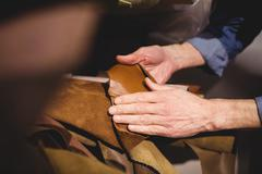 Close up of hands holding leather in the storehouse Stock Photos