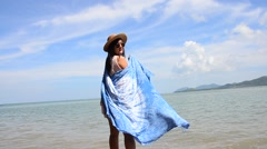 Thai women relax and playing indigo tie dye fabric shawl on the beach Stock Footage