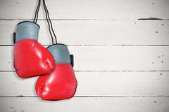 Boxing gloves attached to white background against white wood - stock photo