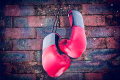 Boxing gloves attached to white background against texture of bricks wall - stock photo
