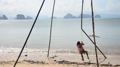 Thai woman playing wooden bamboo swing hilltribe style on the beach Stock Footage