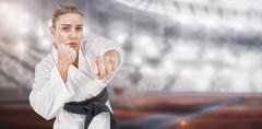 Female athlete practicing judo against composite image of american stadium Kuvituskuvat