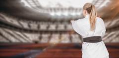 Female athlete practicing judo against digitally generated image of stadium - stock photo